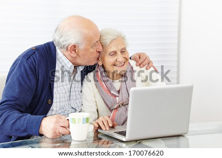 Man kissing happy senior woman at the computer on the cheek - stock photo