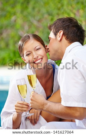 Man kissing happy woman with champagne at pool of hotel in holiday