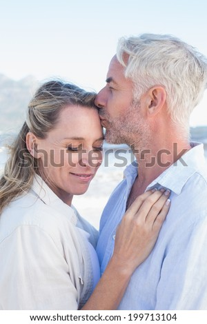 Man kissing his smiling partner on the forehead at the beach on a sunny day