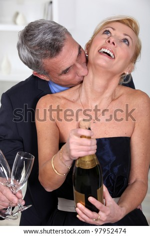Man kissing his wife's neck - stock photo