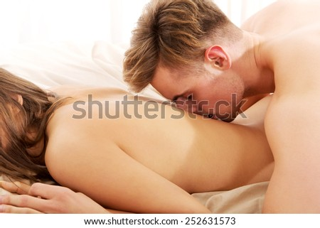 Man kissing woman in her back on bed.