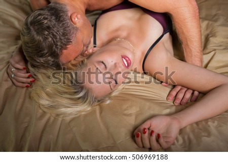 Man kissing woman on her neck during foreplay