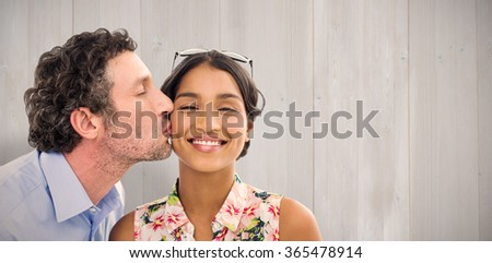 Man kissing woman on the cheek against wooden planks - stock photo