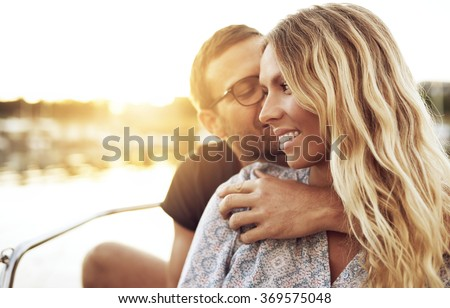 Man Kissing Woman while Woman Smiling Gently - stock photo