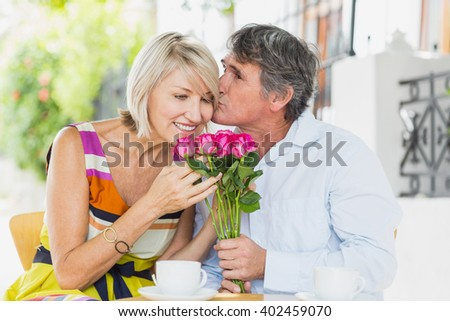 Man kissing woman with flower bouquet at cafe