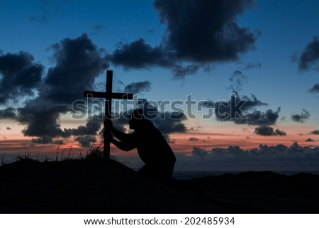 Man kneeling and holding on to a cross.