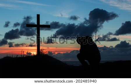 Man kneeling by a cross in prayer as the day finishes. - stock photo
