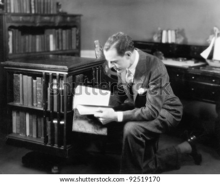 Man kneeling in his home library browsing a book - stock photo