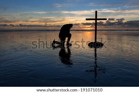 Man kneeling in prayer by a cross on a beach at sunset. - stock photo