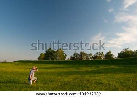 Man kneeling in the middle of huge meadow and observing nature on sunny spring day.