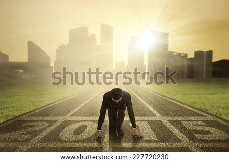 Man kneeling on track and ready to chase his dream in the future 2015 - stock photo