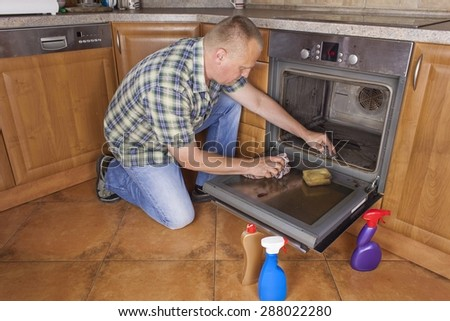 Man kneels on the floor in the kitchen and cleans the oven. Cleaning work in the home. Man helping his wife with maid service. - stock photo
