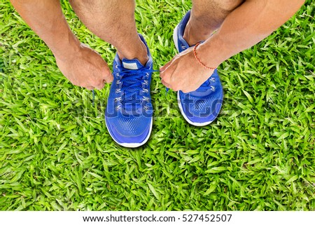Man lacing sport shoes on green grass floor, sport exercise concept