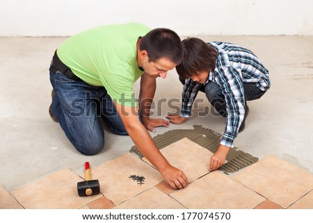 Man laying ceramic floor tiles helped by his son to evenly space the pieces - stock photo