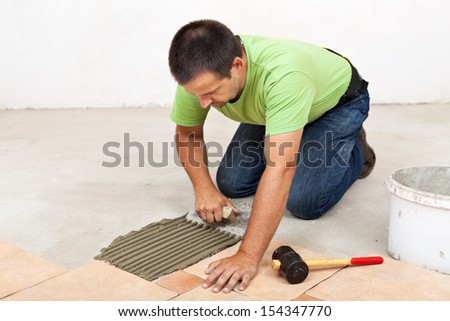 Man laying ceramic floor tiles - spreading the adhesive material - stock photo