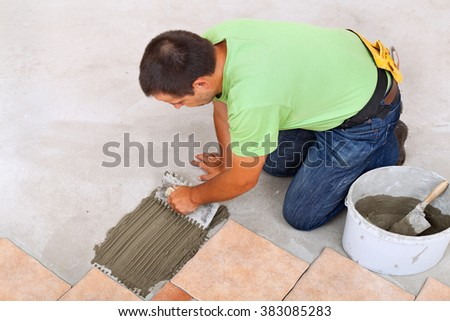 Man laying ceramic tiles floor, spreading the adhesive on the concrete - focus on hands