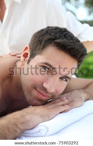 Man laying down a massage bed - stock photo