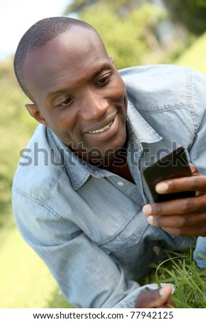 Man laying down in park with mobile phone
