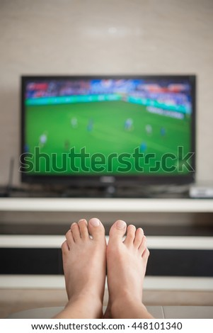 man laying down on a sofa at home watching soccer match on tv
