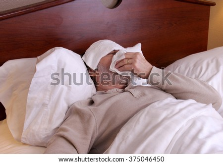 Man laying in bed with a washcloth on his forehead and blowing his nose - stock photo