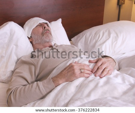 Man laying in bed with a washcloth on his head with a fever and chills - stock photo