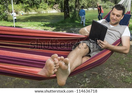 Man laying in hammock and working with tablet, family is playing behind