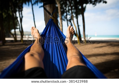 Man Laying in Hammock at Woodline on the Beach - stock photo