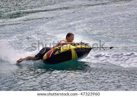 Man laying on inner tube being pulled by a fast boat.