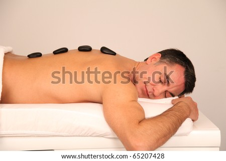 Man laying on massage bed with hot stones on his back