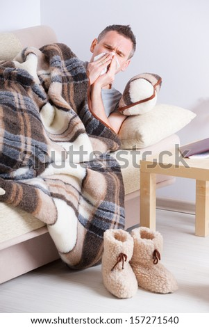 Man laying on sofa uder natural woolen blanket with tissue in his hand