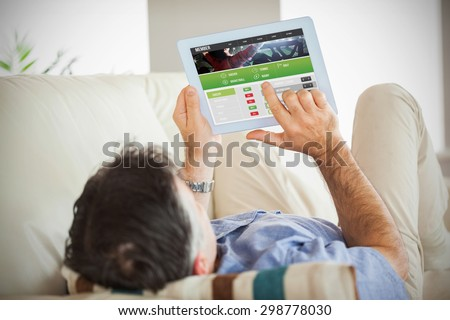 Man laying on sofa using a tablet pc against gambling app screen - stock photo