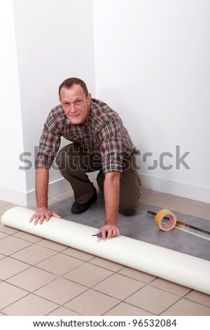 Man laying pvc flooring - stock photo