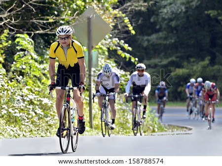 Man leading a group of riders up a mountain road during a race. - stock photo