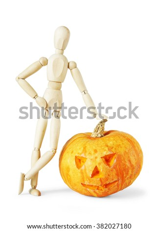 Man leaned against a giant Halloween pumpkin. Abstract image with a wooden puppet - stock photo