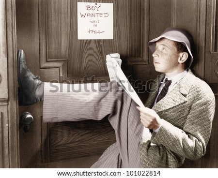 Man leaning against a door with  his legs up and reading a newspaper - stock photo