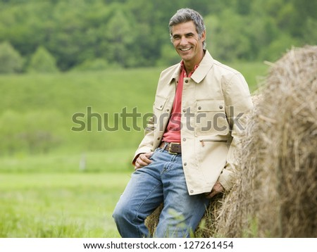 Man leaning against a hay bale