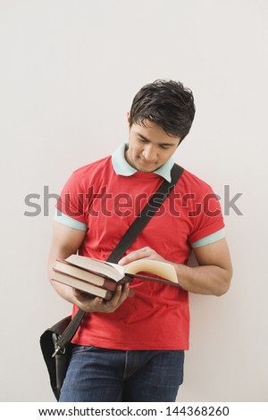 Man leaning against a wall and reading a book - stock photo
