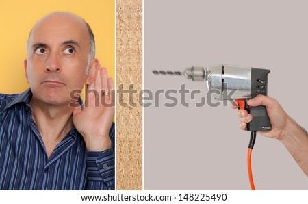 Man leaning against a wall listening to a drill  - stock photo