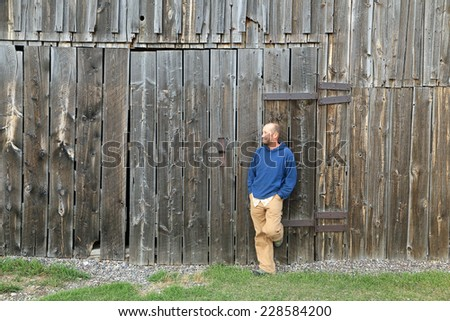 Man leaning against an old wooden barn. - stock photo