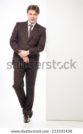 Man leaning against empty board while smiling to camera on white background - stock photo