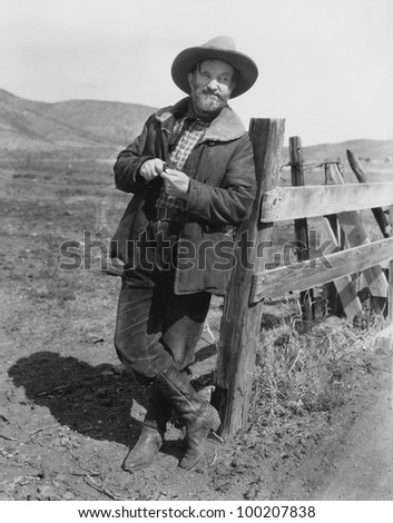 Man leaning against fence post - stock photo