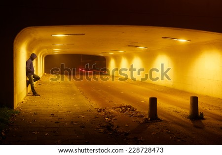 Man leaning against the wall of tunnel on a foggy night while cyclists pass.