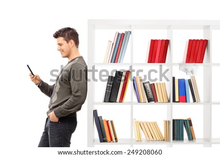 Man leaning on a bookshelf and typing on his phone isolated on white background - stock photo