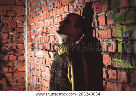 Man leaning on a brick wall in abandoned unfinished house - stock photo
