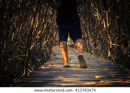 Man legs and feet walking on the wood path in Mangrove forest in Thailand - stock photo