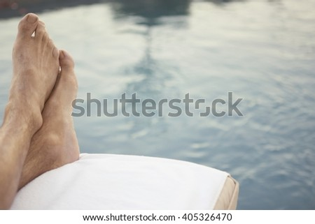 Man legs near pool on relaxing lounge chair
