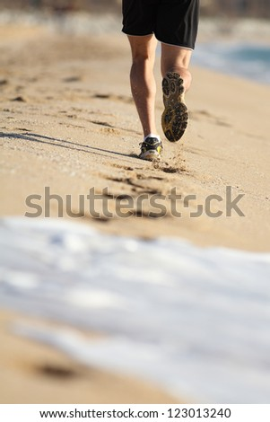 Man legs running on the sand of a beach with water erasing footprints - stock photo
