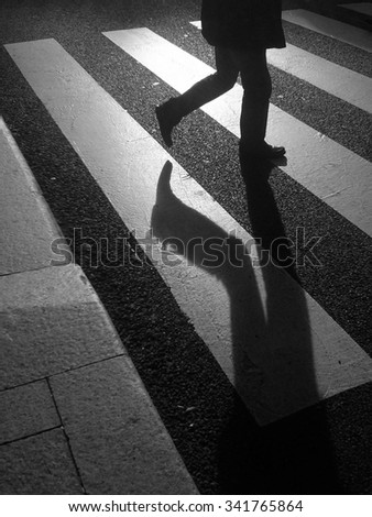 Man legs silhouette and shadow crossing the street in a crosswalk - stock photo