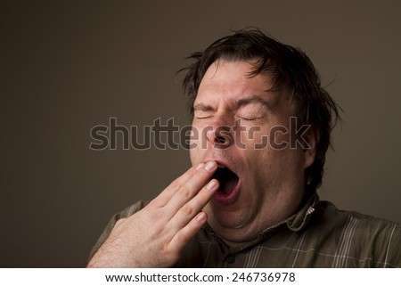MAn lets out a huge yawn with how tired he is, or is he getting ready to sneeze - stock photo