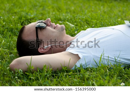 Man lie on the grass with tablet in the park and listening to music - stock photo